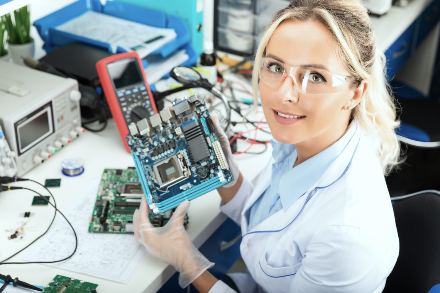 Female electronic engineer holding computer motherboard in hands in the laboratory